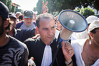 """TUNIS, TUNISIA - 25 JULY 2013: Hedi Abidi (center), lawyer of the """"Groupe des 25"""" and member of the Popular Front, rallies in Avenue Habib Bourguiba in front of the Interior Ministry to protest against the assassination of opposition leader Mohamed Brahmi in Tunis, Tunisia, on July 25th 2013.<br /> <br /> Tunisia, birthplace of the Arab Spring revolutionary movement, was plunged into a new political crisis on Thursday when assassins shot Mohamed Brahmi, 58, leader of the Arab nationalist People's Party, an opposition party leader outside his home in a hail of gunfire.<br /> <br /> The assassination, which coincided with celebrations for the 56th anniversary of Tunisian statehood after independence from France, came as Tunisia was still grappling with a democratic transition following the January 2011 revolution that toppled the country's autocratic leader, Zine el-Abidine Ben Ali, and forced him into exile. The Tunisian revolution was the catalyst that spawned similar uprisings in Egypt, Libya, Yemen and Syria."""