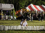 Pine Bush, New York - A girl with an umbrella sits in the grass while waiting to light candles during the Relay for Life on Saturday, June 12, 2010. Luminaries are purchased in memory of someone who lost their battle against cancer, or in honor of a survivor of the disease. The Relay for Life is a fundraiser for the American Cancer Society.