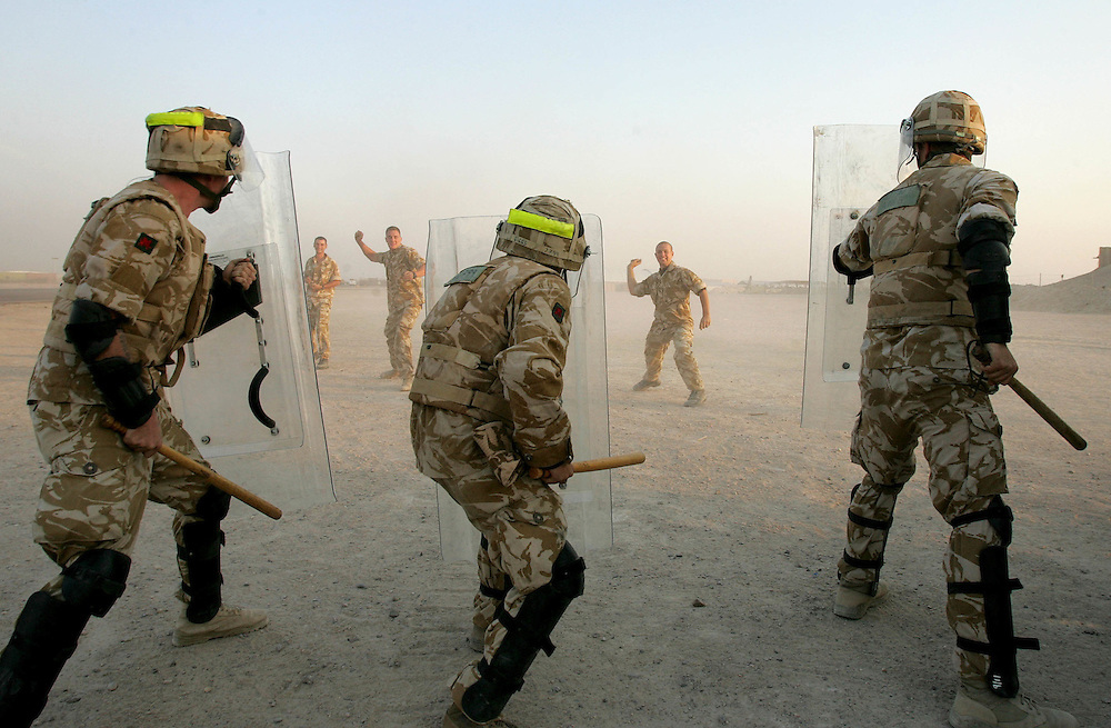 14 October 2005..Basra, Iraq...'Riot Squad'.....Companies from The Royal Regiment of Wales engage in Public Order training. Equipped with wooden batons known as 'hickory sticks', Perspex shields and 'baton guns' which fire a hard rubber bullet the troops take turns to act as a hostile mob...The soldiers deploy from armoured 'snatch' Land Rovers and 'warrior' fighting vehicles. The mob pelts the riot squad with sticks, rocks and bottles whilst shouting abuse. The squad make repeated charges at the crowd, pushing them back and forming a 'base line' which they then try and hold. Often the vehicles are used to push into the mob with the dismounted soldiers running along behind using them as cover. The troops also carry their SA 80 rifles, the 'rules of engagement' allow for an escalation to the use of live ammunition against a mob if the soldiers lives are considered to be in danger. Training in temperatures in excess of 120 F requires that the squad drinks several litres of water during a session. In order to make the training realistic both sides must act aggressively and this does result in injuries. During this session one soldier was evacuated after having his head split open by a baton blow.