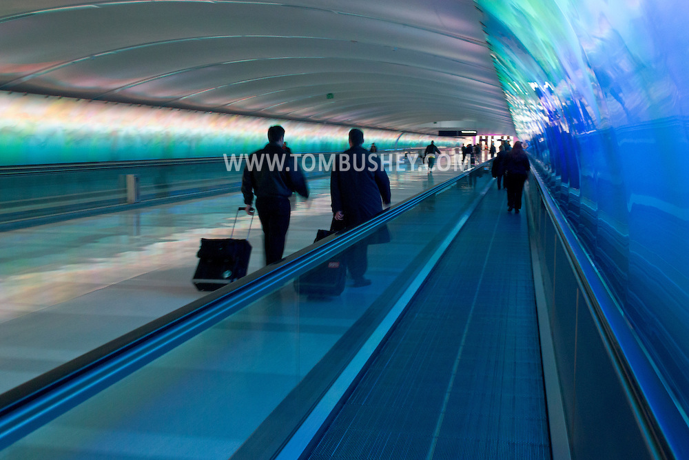 Detroit, Michigan - People walk through the Light Tunnel connecting concourses B and C at Detroit Metropolitan Airport on Feb. 3, 2013. The tunnel features an elaborate multi-colored light show behind sculpted glass as well as moving walkways. The installation, one of the first large-scale uses of color changing LED lighting in the United States, was produced by Mills James Productions with glasswork by Foxfire Glass Works of Pontiac, Michigan.