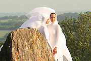 Two women in white costumes stood at the stone circle, Glastonbury 2005