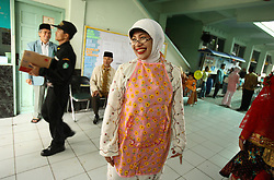 Midwife Hdjella, 57, smiles after a morning of circumcisions in Bandung, Indonesia on April 23, 2006. The families of 248 girls were given money to have their children circumcised in a mass circumcision celebration timed to honour the Prophet Mohammed's birthday. While religion was the main reason for circumcisions, it is believed by some locals that a girl who is not circumcised would have unclean genitals after she urinates which could lead to cervical cancer. It is also believed if one prays with unclean genitals their prayer won't be heard. The practitioners used scissors to cut the hood and tip of the clitoris. The World Health Organization has deemed the ritual unnecessary and condemns such practices.