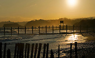 Winter sun over Dawlish Warren, Exe Estuary, South Devon, UK.  Low sunlight  silhouettes wooden groynes and casts a warm glow across the sand.