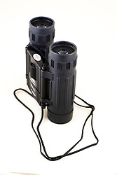 26 July 2006 a hand sized pair of binoculars with a neck strap shot in a light tent on a fabric background.