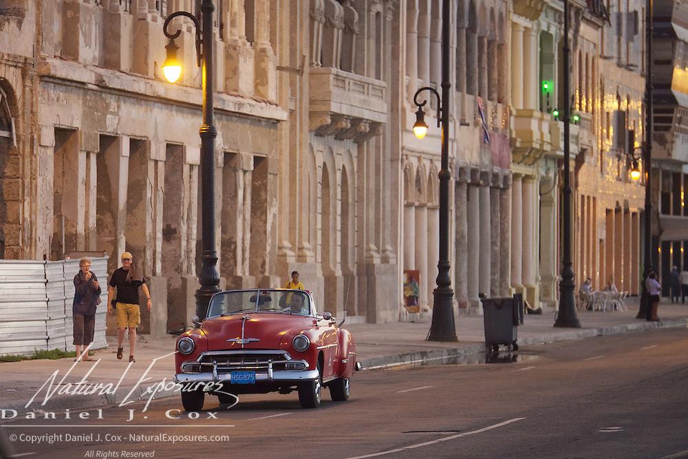 A vintage car on the streets of Havana, Cuba driving on the busy avenue that runs alongside Havana's Malecon. Cuba