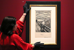 "© Licensed to London News Pictures. 08/04/2019. London, UK. A staff member hangs Edvard Munch's ""The Scream, 1895"" - which developed from an episode represented in Despair, but with the central figure turned to face the viewer. The swirling reddish-blue clouds are translated in this print into compressed undulating bands of black and white that emphasise the acute panic expressed by the figure. In a twist of fate, Munch's sister Laura was diagnosed in 1894 with schizophrenia and institutionalised in a hospital near the site of The Scream. <br /> <br /> The work of Norwegian artist Edvard Munch (1863-1944) - ""Edvard Munch: love and angst"" at the British Museum opens from 11 April until 21 July 2019. The exhibition focus on Munch's remarkable and experimental prints – an art form which made his name and at which he excelled throughout his life – and will examine his unparalleled ability to depict raw human emotion. It will be the largest exhibition of Munch's prints in the UK for 45 years. Photo credit: Dinendra Haria/LNP"