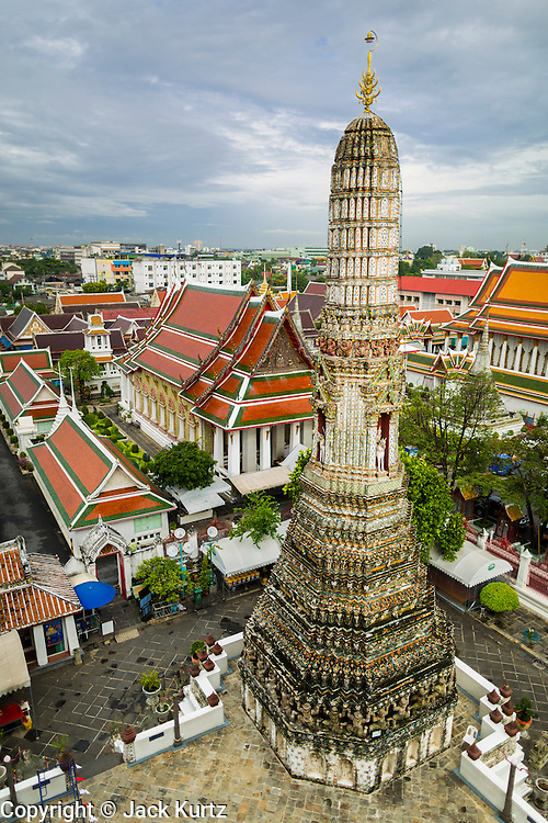"""23 SEPTEMBER 2013 - BANGKOK, THAILAND:     A satellite prang the supports the famous central prang at Wat Arun. The full name of the temple is Wat Arunratchawararam Ratchaworamahavihara. The outstanding feature of Wat Arun is its central prang (Khmer-style tower). The world-famous stupa, known locally as Phra Prang Wat Arun, will be closed for three years to undergo repairs and renovation along with other structures in the temple compound. This will be the biggest repair and renovation work on the stupa in the last 14 years. In the past, even while large-scale work was being done, the stupa used to remain open to tourists. It may be named """"Temple of the Dawn"""" because the first light of morning reflects off the surface of the temple with a pearly iridescence. The height is reported by different sources as between 66,80 meters and 86 meters. The corners are marked by 4 smaller satellite prangs. The temple was built in the days of Thailand's ancient capital of Ayutthaya and originally known as Wat Makok (The Olive Temple). King Rama IV gave the temple the present name Wat Arunratchawararam. Wat Arun officially ordained its first westerner, an American, in 2005. The central prang symbolizes Mount Meru of the Indian cosmology. The temple's distinctive silhouette is the logo of the Tourism Authority of Thailand.       PHOTO BY JACK KURTZ"""
