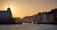 Sunset and boats in Nyhavnsbroen, Copenhagen, Denmark.