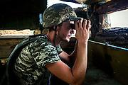 A soldier using binoculars is watching over the frontline of Hranitne, near Mariupol, southeast Ukraine.
