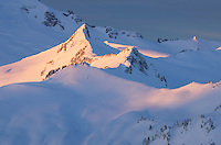 Coleman Pinnacle in the Mount Baker Wilderness of Washington glows in the dawn light of a winter morning.