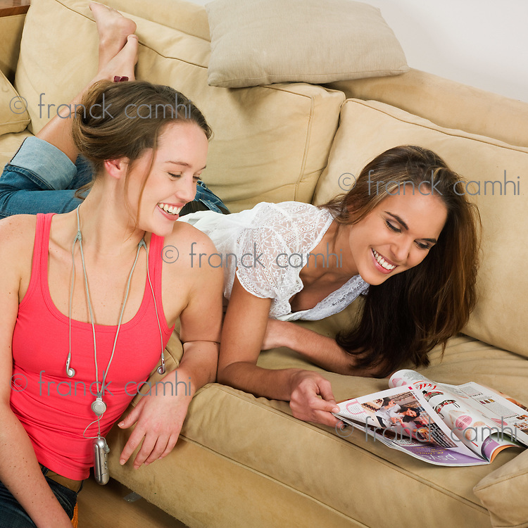 pictures in a living room of two young girls sitting on a couch watching magazine