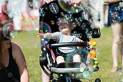 © Licensed to London News Pictures. 13/06/2014. Isle of Wight, UK.   A baby gets excited about giant bubbles at Isle of Wight Festival 2014.   The Isle of Wight festival is an annual music festival that takes place on the Isle of Wight. Photo credit : Richard Isaac/LNP