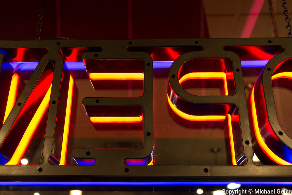 color photograph of neon open sign at night shot from behind