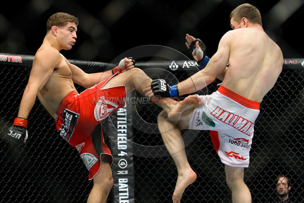 """MANCHESTER, ENGLAND, OCTOBER 26, 2013: Al Iaquinta (red shorts) and Piotr Hallmann (white shorts) compete during """"UFC Fight Night 30: Machida vs. Munoz"""" inside Phones4U Arena in Manchester, England (© Martin McNeil)"""