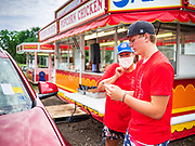 "26 JUNE 2020 - DES MOINES, IOWA: BRENDA SMITH PARISH and HUNTER (first name only) review a customer's order on Hunter's smart phone at abooth selling fried potatoes and pork tenderloin sandwiches at Fair Food Friday in Des Moines. The 2020 Iowa State Fair, like many state fairs in the Midwest, has been cancelled this year because of the COVID-19 (Coronavirus) pandemic. The cancellation of the fair left many small vendors stranded with no income. Some of the fair food vendors in Iowa started ""Fair Food Fridays"" on a property a few miles south of the State Fairgrounds. People drive up and don't leave their cars while vendors bring them the usual midway fare; corndogs, fried tenderloin sandwiches, turkey legs, deep fried Oreos, lemonaide and smoothies. Fair Food Friday has been very successful. The vendors serve 450-500 people per Friday and during the lunch rush people wait in line in their cars 30 - 45 minutes to place an order.      PHOTO BY JACK KURTZ"