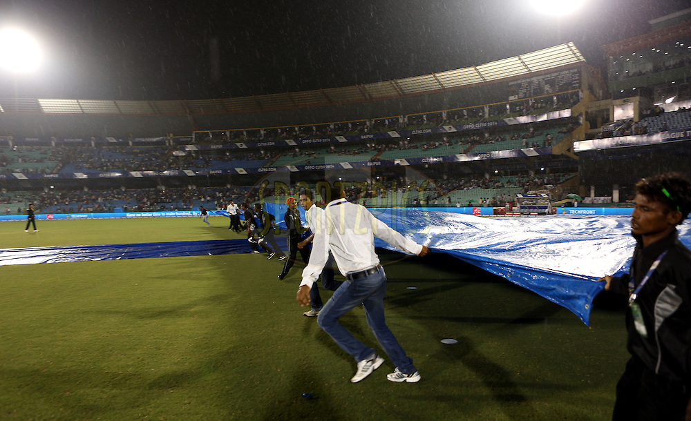Ground staff seen at work as rains stops the play during match 3 of the Oppo Champions League Twenty20 between the Cape Cobras and the Northern Knights held at the Chhattisgarh International Cricket Stadium, Raipur, India on the 19th September 2014<br /> <br /> Photo by:  Sandeep Shetty / Sportzpics/ CLT20<br /> <br /> <br /> Image use is subject to the terms and conditions as laid out by the BCCI/ CLT20.  The terms and conditions can be downloaded here:<br /> <br /> http://sportzpics.photoshelter.com/gallery/CLT20-Image-Terms-and-Conditions-2014/G0000IfNJn535VPU/C0000QhhKadWcjYs