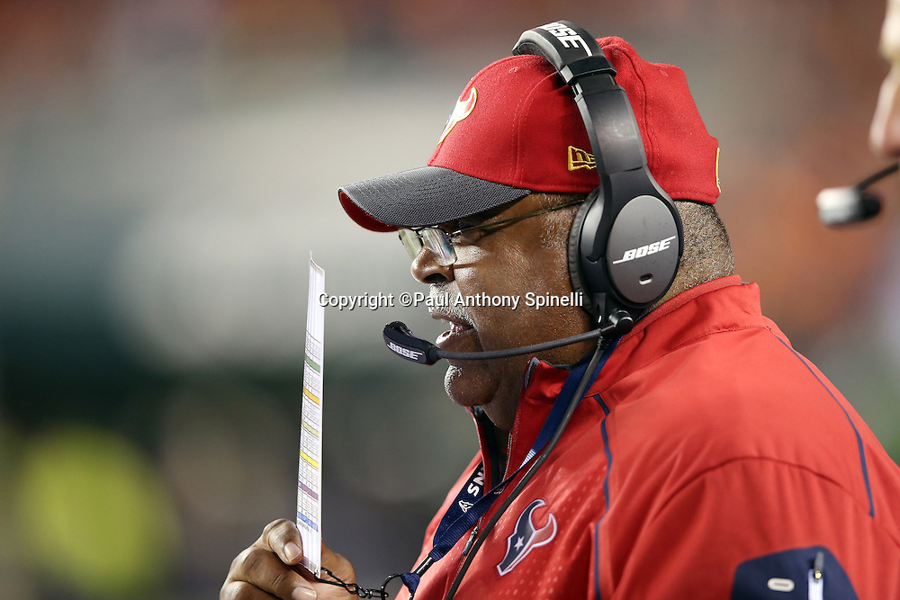 Houston Texans defensive coordinator Romeo Crennel hides his mouth with his play chart as he talks on his headsets on the sideline during the 2015 week 10 regular season NFL football game against the Cincinnati Bengals on Monday, Nov. 16, 2015 in Cincinnati. The Texans won the game 10-6. (©Paul Anthony Spinelli)