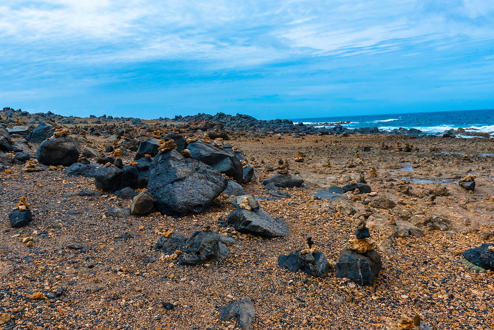 A wide angle shot of a beach covered in rocks, large and small.