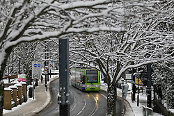 © Licensed to London News Pictures. 21/01/2013, London, UK. A tram runs along a snow covered street in Croydon, South London, Monday, Jan. 21, 2013. Britain is continue affect by cold weather and snow. Photo credit : Sang Tan/LNP