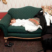A five-year-old Caucasian boy sleeping on a green couch in a hotel lobby. His tuxedo is tossed off to the side and his black shoes are side by side on the floor.