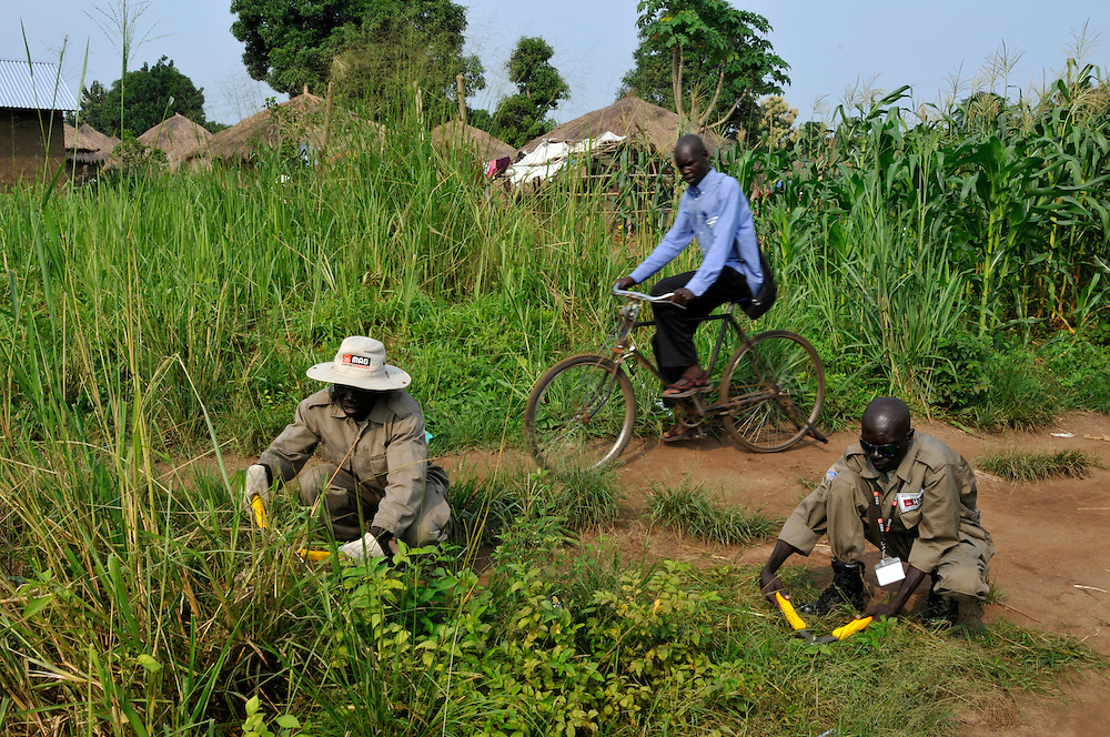 Deminers from Mines Advisory Group (MAG) prepare to control an area of the village for unexploded ordinance to allow for the drilling of bore holes and the installation of water towers. The village has no potable water or public services..Yei, South Sudan. 27/06/2011..Photo © J.B. Russell