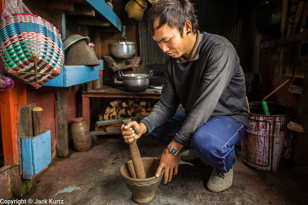23 APRIL 2014 - CHIANG KHONG, CHIANG RAI, THAILAND: A crewman makes a chili dip for lunch on a riverboat that hauls freights between Chiang Khong, Thailand and Luang Prabang, Laos. It takes the boats two and a half days to make the voyage. Luang Prabang is as far downriver as boats can go in the dry season because the river becomes unnavigable due to rocks and sandbars. Chiang Rai province in northern Thailand is facing a drought this year. The 2014 drought has been brought on by lower than normal dry season rains. At the same time, closing dams in Yunnan province of China has caused the level of the Mekong River to drop suddenly exposing rocks and sandbars in the normally navigable Mekong River. Changes in the Mekong's levels means commercial shipping can't progress past Chiang Saen. Dozens of ships are tied up in the port area along the city's waterfront.              PHOTO BY JACK KURTZ