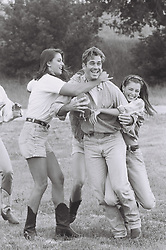 man being tackled by girls while playing football