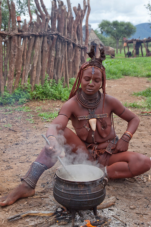 Viahondjera Musutua, a Himba tribeswoman, cooks at her home in the small village of Ondjete in northwestern Namibia. (Viahondjera Musutua is featured in the book What I Eat: Around the World in 80 Diets.) MODEL RELEASED.