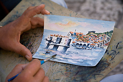 Europe, Croatia, Dalmatia, Dubrovnik.  Hands painting watercolor of Dubrovnik's historic house and forts, and Adriatic Sea,