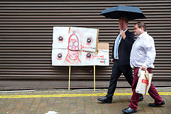 © Licensed to London News Pictures. 06/10/2015. Manchester, UK. Tory delegates walking past an anti-austerity placard outside Conservative Party Conference at Manchester Central convention centre on Tuesday, 6 October 2015. Photo credit: Tolga Akmen/LNP