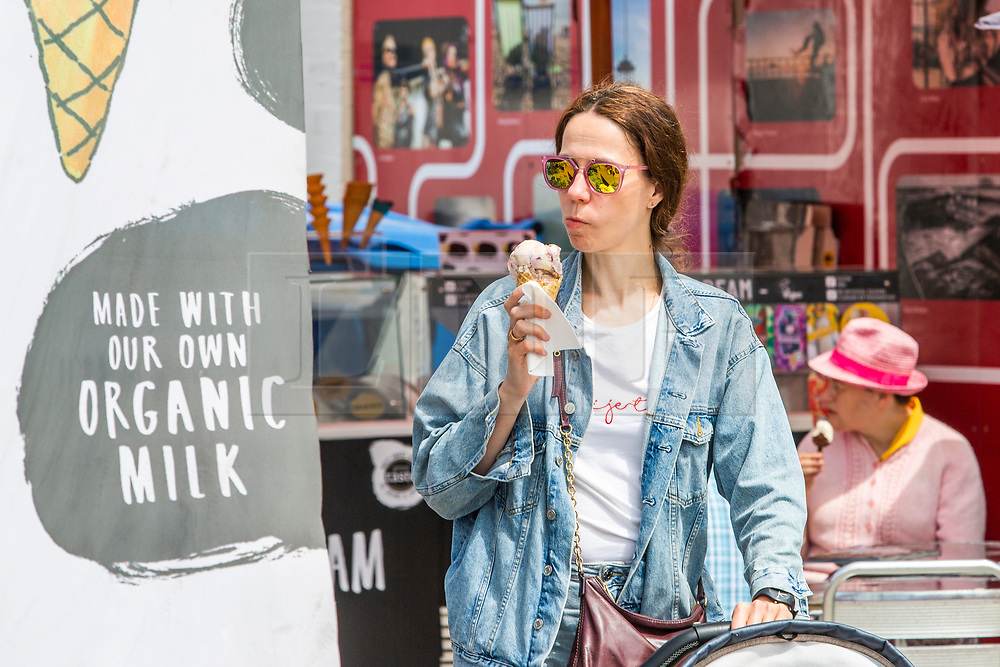© Licensed to London News Pictures. 02/06/2019. Brighton, UK. A member of the public enjoys an ice cream on the Bach in Brighton and Hove. Photo credit: Hugo Michiels/LNP