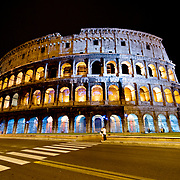 A wide-angle shot of Rome's famous and historic Coliseum under lights at night from across the street.