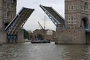 boat passing under London bridge