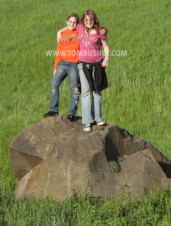 Salisbury Mills, NY  - A 10-year-old girl and her 12-year-old sister stand on a rock in a field while hiking on May 10, 2009.