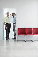 Two men talking in doorway