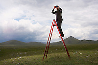 Businessman with Binoculars on Ladder