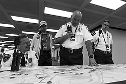 Scotty Everitt, Pittsburgh EMS Paramedic and Division Chief, left, smiles as Dr. Ron Roth, Marathon Medical Director, center left, Mark Tomassi, Pittsburgh EMS Paramedic and District Chief, center, and Robert Farrow, right, Chief of Pittsburgh EMS, observe a tactical map of the race course.