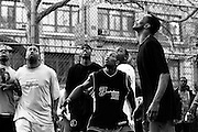 "April 6th 2005. New York, New York. United States..Located in the heart of Greenwich Village, the West 4th Street basketball Court, known as ""The Cage"", offers no seating but attracts the best players and a lot of spectators as soon as spring is around the corner..Half the size of a regular basketball court, it creates a fast, high level of play. The more people watch, the more intense the games get. « The Cage » is a free show. Amazing actions, insults and fights sometimes, create tensions among and inside the teams. The strongest impose their rules. Charisma is present..""The Cage"" is a microcosm. It's a meeting point for the African American street culture of New York. Often originally from Jamaica or other islands of the Caribbean, they hang out, talk, joke, laugh, comment the game, smoke… Whether they play or not, they're here, inside ""The Cage"". Everybody knows everybody, they all greet each other, they shake hands and hug: ""Yo, whasup man?"""