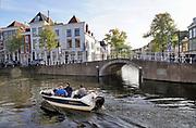 Nederland, Leiden, 29-9-2018In de binnenstad van de stad vaar een kleine motorboot door de gracht van het Rapenburg. Drie mannen zitter er in. Een bruggetje geeft toegang tot een andere gracht.Foto: Flip Franssen
