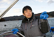 Takeshi Tachibana of Oh! Guts! stands aboard a fishing boat in Ogatsu Bay, Ishinomaki, Miyagi Prefecture, Japan on 01 Dec 2011. .Photographer: Robert Gilhooly
