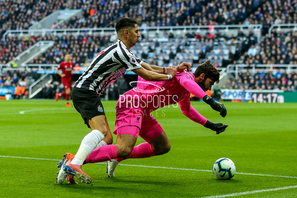 Ayoze Perez (#17) of Newcastle United fouls Alisson Becker (#13) of Liverpool during the Premier League match between Newcastle United and Liverpool at St. James's Park, Newcastle, England on 4 May 2019.
