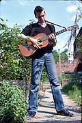 Scott Burnel with Guitar in the Garden, 16 Hawthorne Rd, High Wycombe, UK, 1980s.