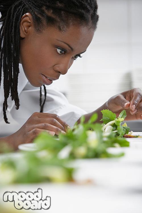 Female chef preparing salad in kitchen