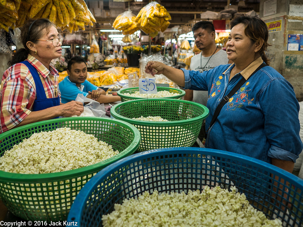 """11 AUGUST 2016 - BANGKOK, THAILAND:  A vendor (left) sells flower buds for garlands to customer in Pak Khlong Talat in Bangkok. Pak Khlong Talat (literally """"the market at the mouth of the canal"""") is the best known flower market in Thailand. It is the largest flower market in Bangkok. Most of the shop owners in the market sell wholesale to florist shops in Bangkok or to vendors who sell flower garlands, lotus buds and other floral supplies at the entrances to temples throughout Bangkok. There is also a fruit and produce market which specializes in fresh vegetables and fruit on the site. It is one of Bangkok's busiest markets and has become a popular tourist attraction.      PHOTO BY JACK KURTZ"""