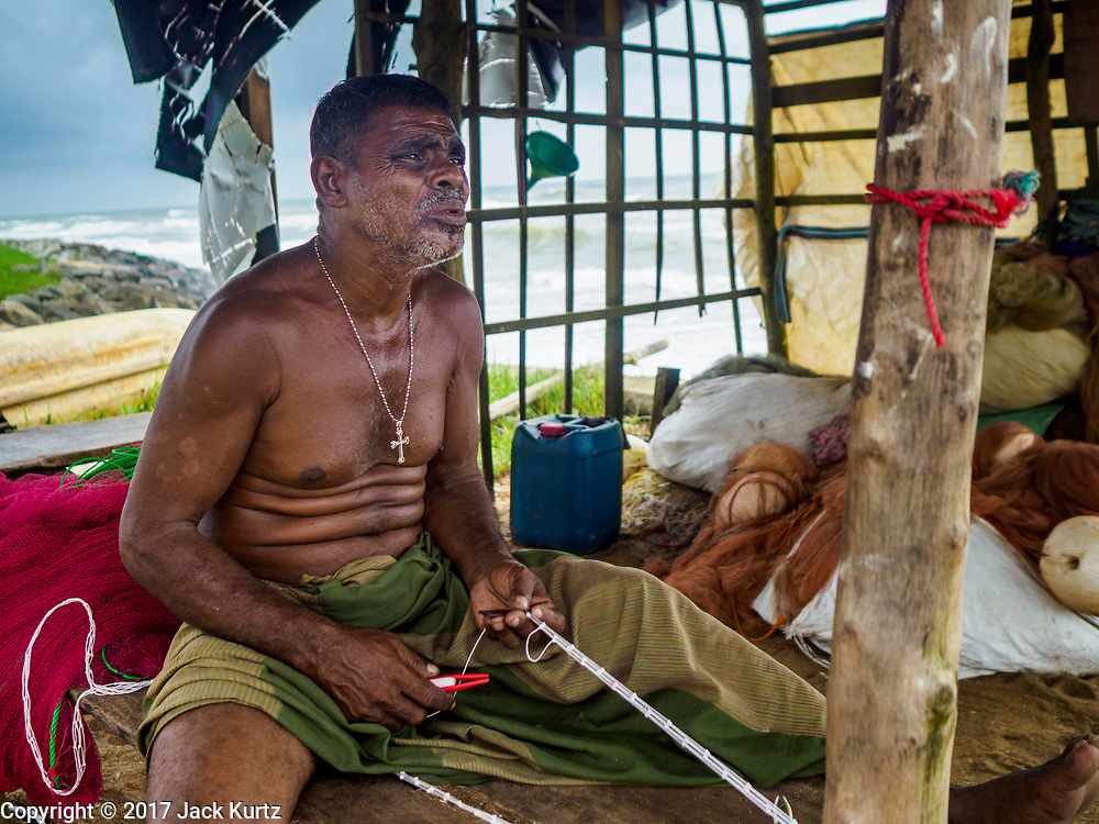 07 OCTOBER 2017 - MORATUWA, SRI LANKA: A fisherman repairs his nets in a small hut on the beach in Moratuwa, a fishing village south of Colombo. Fish is an important source for many Sri Lankans.  PHOTO BY JACK KURTZ