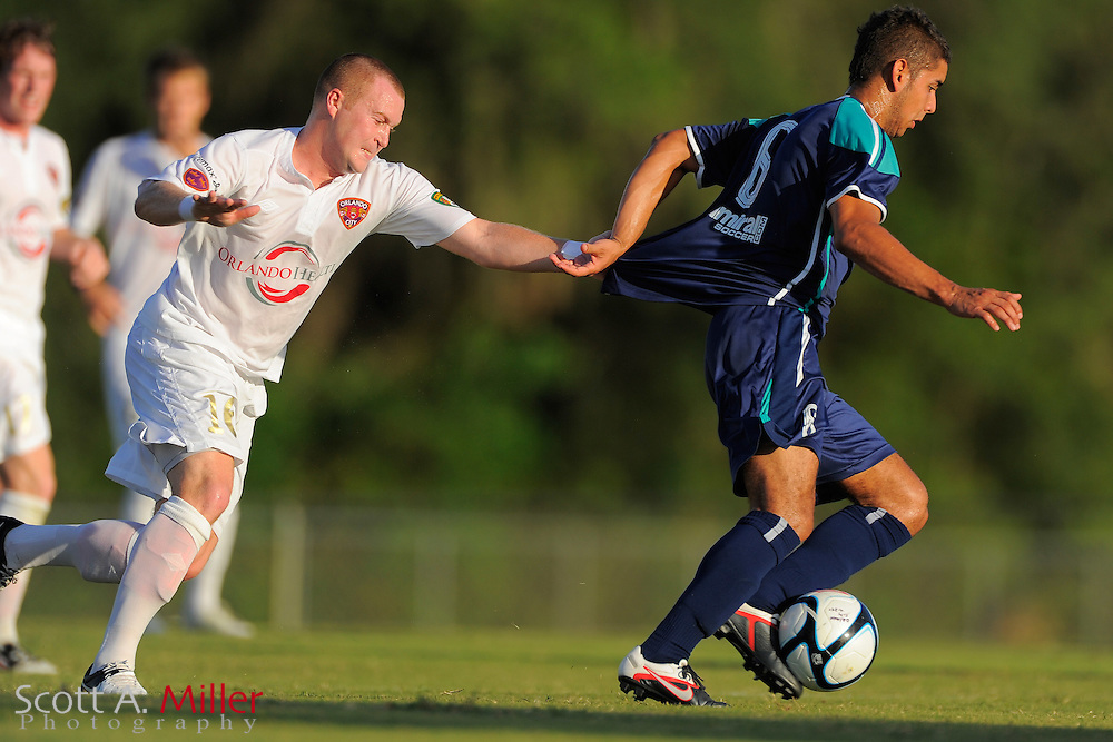 Orlando City midfielder Sam Fairhurst (16) grabs the jersey of VSI Tampa Flames midfielder Andres Navas (8) as he runs upfield during their Premier Development League game at the Seminole Soccer Complex on July 13, 2012 in Sanford, Florida. ..©2012 Scott A. Miller