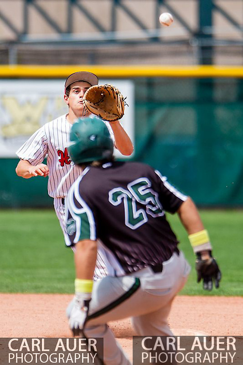 May 17th 2013: Holly Wildcats junior Jason Barth (21) eyes the ball as he catches Fleming Wildcats senior Trevor Chintala (25) in a pickle between 1st and 2nd during the CHSAA 1A Baseball final against the Holly Wildcats at All Star Park in Lakewood, Colorado