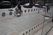 Cyclists pedal past an office foyer entrance featuring dots and circles on exterior windows in the City of London.