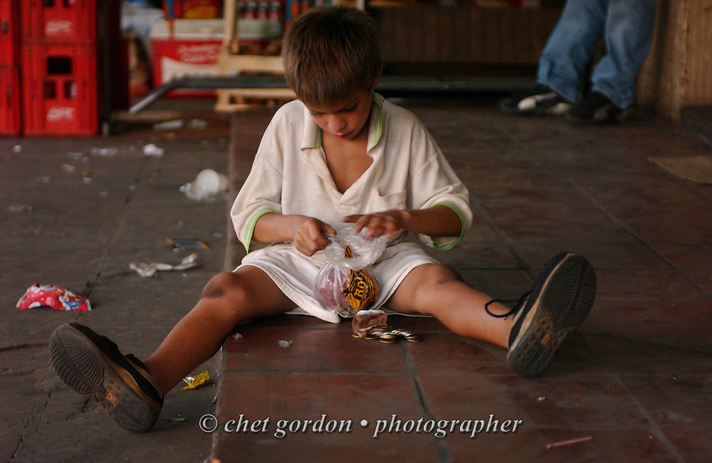 ASUNCION, PARAGUAY. Young Paraguayan street boy counts his earnings on a street corner in Asuncion, Paraguay on Wednesday evening, March 15, 2006. Hundreds of street children, some as young as 4 years old and their parents, work the diesel fumed streets of the capital city by squeegeeing windshields, panhandling and selling various items to drivers.