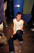 A gormless man sits on floor in nightclub, U.K, 2000s.